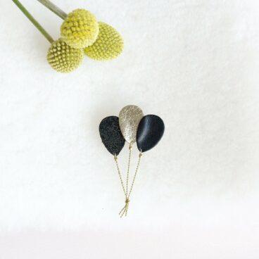 broche de createur en forme de ballons noirs et dorés